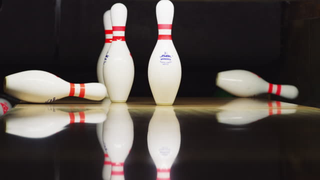 ten bowling pins stand at the end of an alley; bowling ball approaches and knocks down seven. - ten pin bowling stock videos & royalty-free footage