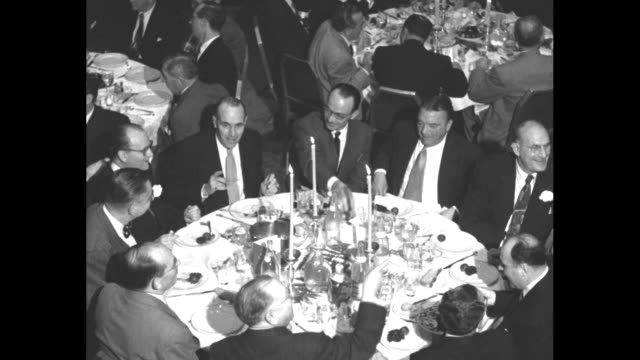 ten men seated at a round table / harry cohn speaking at the podium introduces albert warner with the 3 warner brothers seated to the right - waldorf astoria stock videos & royalty-free footage