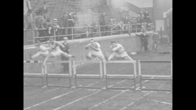 MLS ten meter high hurdlers take off from starting blocks after man in left foreground fires starter pistol and onlookers peer over railing / LS...
