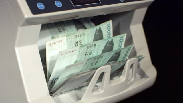 CU SLO MO Ten thousand korean won notes in money counting machine / Seoul, South Korea
