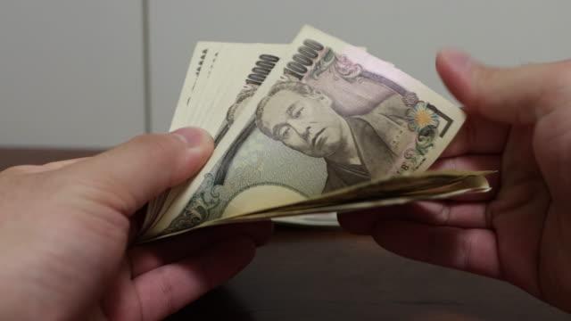 日本通貨の1万円札 - 稼ぐ点の映像素材/bロール