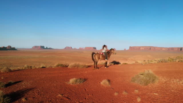 ten year old native american navajo boy with very long hair bareback horseback riding in the northern arizona desert near monument valley tribal park at dusk in the summer - navajo culture stock videos & royalty-free footage
