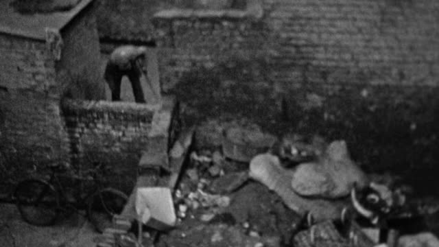 1937 montage tenant sweeping courtyard, slum tenement building and large pile of rubbish, and funeral party carrying flower topped coffin to waiting horse and carriage / london, england, united kingdom - 棺点の映像素材/bロール