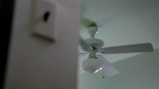 vídeos de stock, filmes e b-roll de a tenant turns on a ceiling fan with a light switch. - energy efficient
