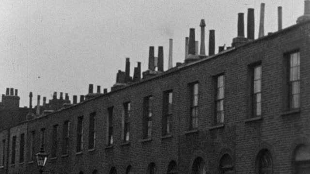 1937 montage tenement and row houses, communities with tenants sitting on stoops, laundry hanging from terraces, and children playing on sidewalks and in the streets / london, england, united kingdom - house rental stock videos & royalty-free footage
