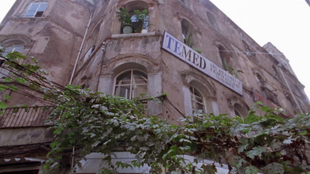 la ms tenement building/ tu over street/ td peasant woman walking on street with large bundle of flowers/ istanbul - low angle view stock videos & royalty-free footage
