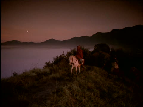 pan of tengarese men riding horses past camera in mtns at dawn / mt bromo in background / indonesia - pflanzenfressend stock-videos und b-roll-filmmaterial