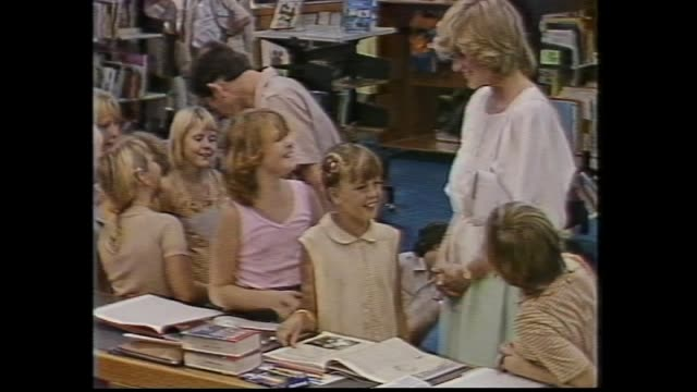 vídeos y material grabado en eventos de stock de kids waving australian flags / princess diana meet and greet mostly indigenous people / prince charles with school girl flips through her book /... - 1983
