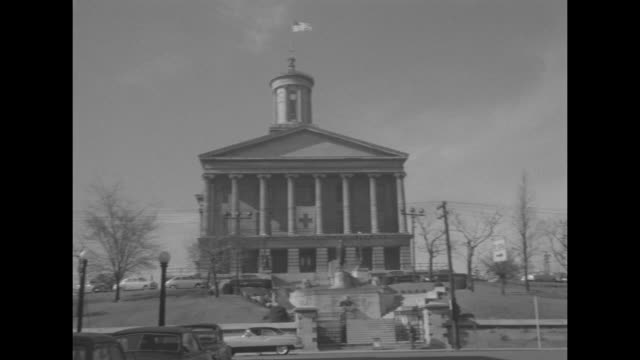 Tennessee State Capitol building with US flag fluttering in breeze at top and traffic moving past on street in foreground / stars of About Face film...