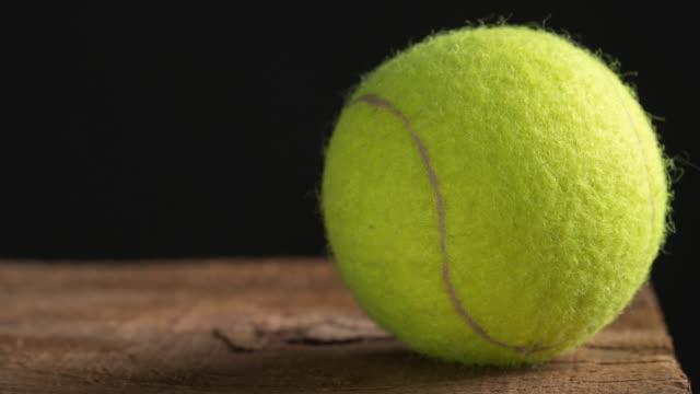 Bola de tênis contra preto sobre a mesa de madeira