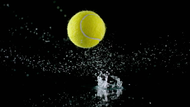 slo mo ld tennis ball bouncing off a wet surface and water splashing - bouncing stock videos & royalty-free footage