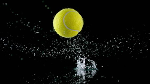 slo mo ld tennisball springt von einer nassen oberfläche und wasser spritzen - hohe aufnahmegeschwindigkeit stock-videos und b-roll-filmmaterial