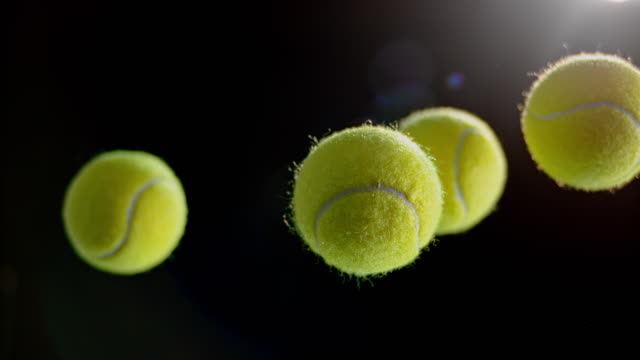 slo mo ld tennis balls in the air on black background - tennis ball stock videos & royalty-free footage