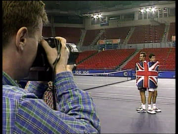 davis cup; itn england: birmingham indoor arena: tim henman practising with greg rusedski henman & rusedski standing for photocall wrapped in union... - davis cup stock-videos und b-roll-filmmaterial