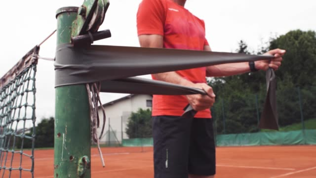 tennis playar warming up with elastic band - tennis ball stock videos & royalty-free footage