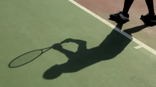 a tennis player casts a shadow as he serves a ball. - serving sport stock videos and b-roll footage