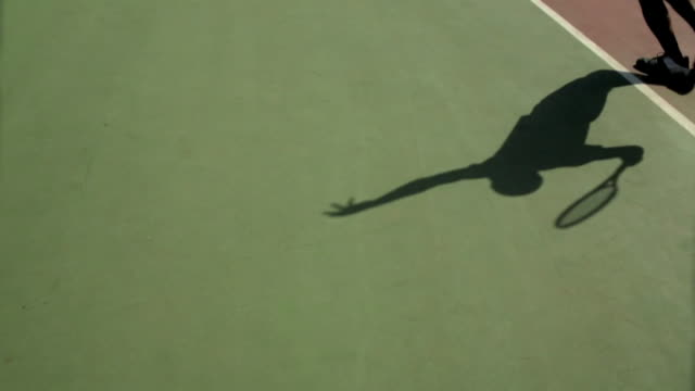 a tennis player casts a shadow on a tennis court in california. - tennis stock videos & royalty-free footage