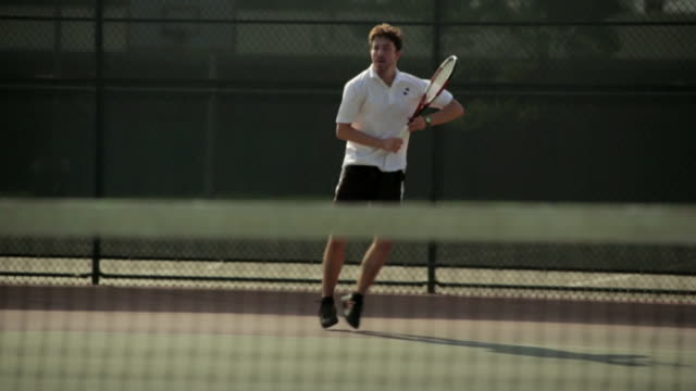 a tennis player moves around as he uses his forehand to volley. - forehand stock videos & royalty-free footage