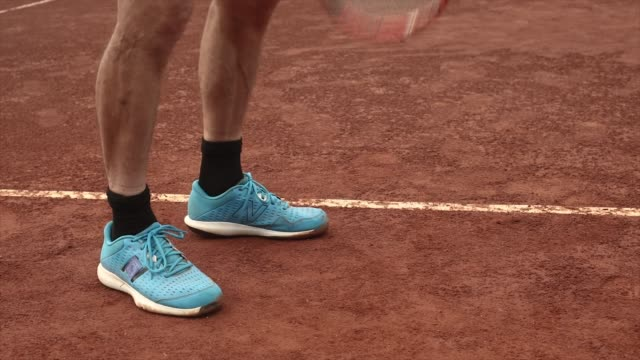 tennis player on red clay court bounces ball at baseline close up - human foot stock videos & royalty-free footage