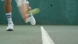 A Tennis player playing a shot off the baseline.