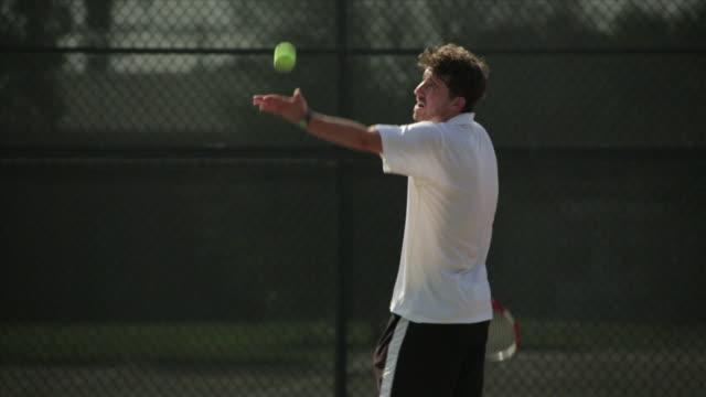 A tennis player serves a ball on a court.
