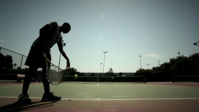 a tennis player serves the ball cross-court. - service stock videos & royalty-free footage