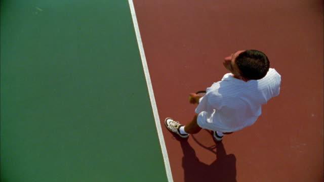 A tennis player serves the ball.