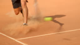 A Tennis player slides across a clay court to play a shot.