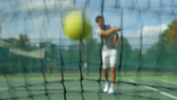 A Tennis player smashes a ball into the net, throws his racket to the ground and kicks the air.