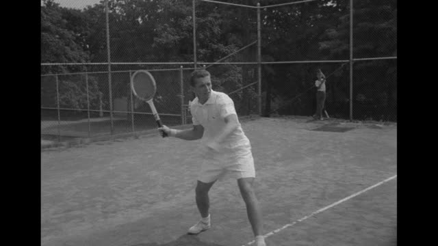 tennis player tony trabert practices on tennis court in ohio / cu trabert's hands demonstrate his forehand grip on tennis racquet / cu trabert's... - backhand bildbanksvideor och videomaterial från bakom kulisserna