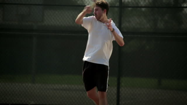 a tennis player tugs at his shirt after he volleys with a forehand stroke. - forehand stock videos & royalty-free footage