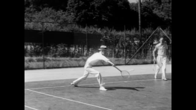 / tennis players dressed in white playing with or next to swedish king gustaf on the court / crowd watches the doubles match / cu of king gustaf... - king royal person stock videos & royalty-free footage
