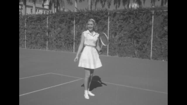 tennis pro fred perry shows joan how to hold her racket she wears a pique tennis dress / ms he shows her how to swing the racket / joan swings at... - racket stock videos and b-roll footage