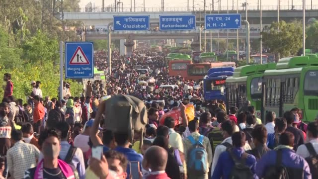 tens of thousands of migrant workers and their families fight their way onto buses organised by india's most populous state to get them to their... - emigration och immigration bildbanksvideor och videomaterial från bakom kulisserna