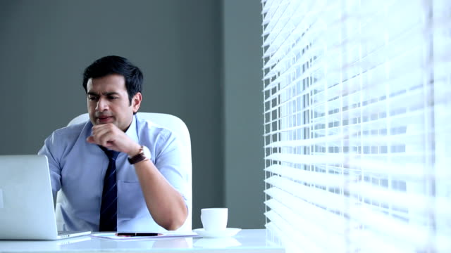 Tensed businessman working on computer, Delhi, India