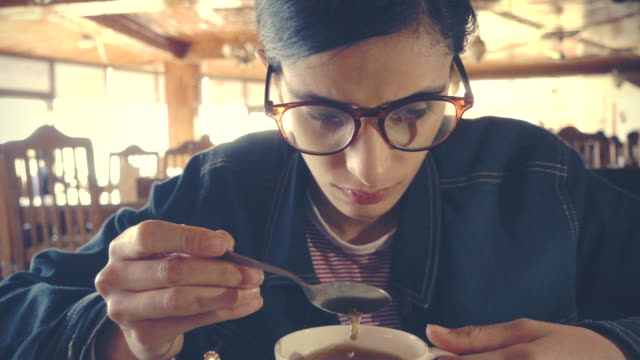 tensed young woman stirs coffee while contemplates deeply in a restaurant. - focus on background stock videos & royalty-free footage