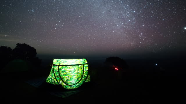 Tent glows under a night sky full of stars