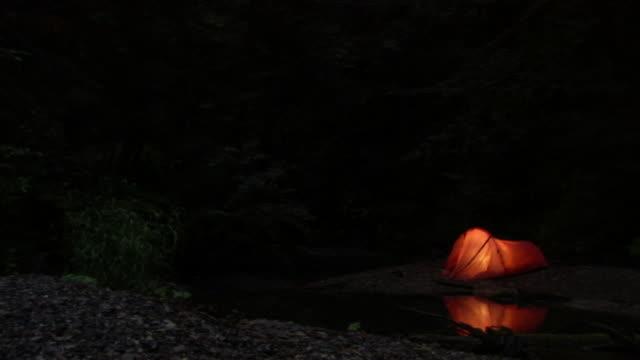 vidéos et rushes de a tent stands beside a stream in a forest. - tente