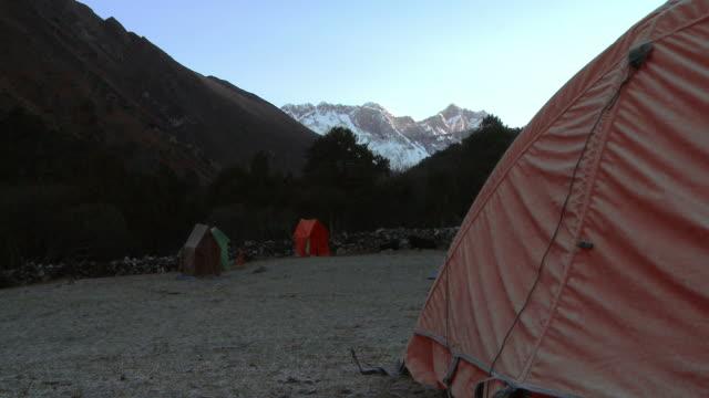 tents pitched at the base of morning sunlit himalayan mountains. - basläger bildbanksvideor och videomaterial från bakom kulisserna