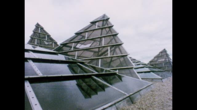 terence conrans industrial designs / uk / geometric solid polygons sit in a mirror / people walk in front of circular atrium / geometric solid... - bordsyteinspelning bildbanksvideor och videomaterial från bakom kulisserna