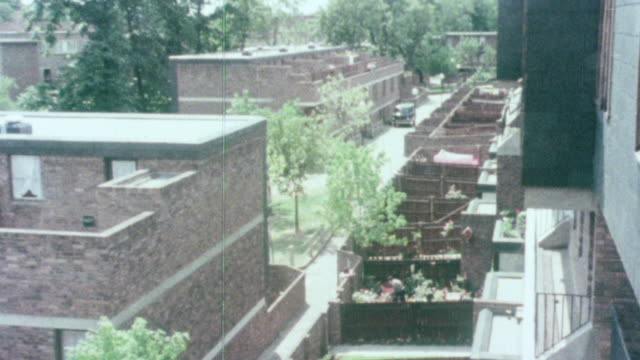 1976 montage terrace housing complexes and tenants enjoying private ground level gardens and upper floor common area breezeways / united kingdom - 1976 bildbanksvideor och videomaterial från bakom kulisserna