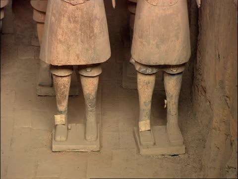 terracotta warriors feet, tilt up to rest of body, museum of qin, xian, china - terrakotta armee stock-videos und b-roll-filmmaterial