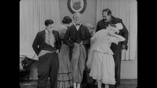 1920 terrified bride and groom fumble with clothing until judge's pants fall down and everyone sits on floor for ceremony - 無声映画点の映像素材/bロール