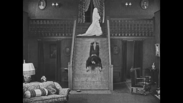 vídeos de stock, filmes e b-roll de 1921 terrified man (buster keaton) tries to avoid bedsheet ghosts by traversing booby-trapped staircase - fantasma