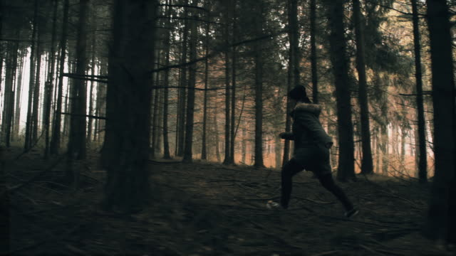 Terrified young woman running through the forest