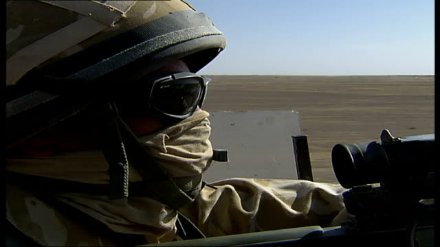 army base life point of view from bulletproofed army truck as drives in armoured convoy through desert landscape ta soldier on lookout post with gun... - army helmet stock videos & royalty-free footage