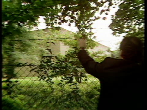 bomb mill hill barracks; cbv man holds barbed wire above wire mesh fence zoom in lms 2 police officers along through grounds l-r as seen through trees - wire mesh fence stock videos & royalty-free footage