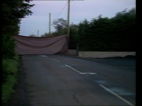 terrorism ira men arrested mist n ireland lms plastic sheet spread across road co tyrone obscure view of shot terrorists' car nr omagh zoom in... - terrorismus stock-videos und b-roll-filmmaterial