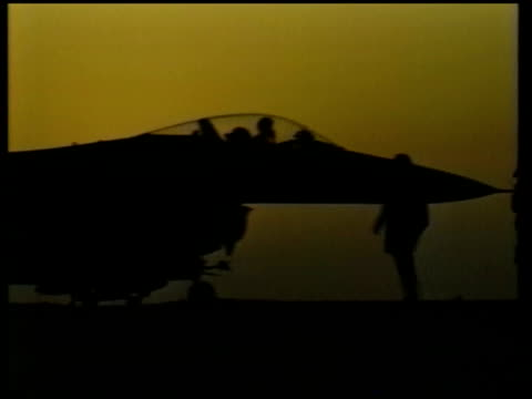 Terrorism Suicide bomb attacks Many dead LIB Silhouette of fighters jets at base as sun sets in b/g Pilots in cockpits of planes LA Man lowering...