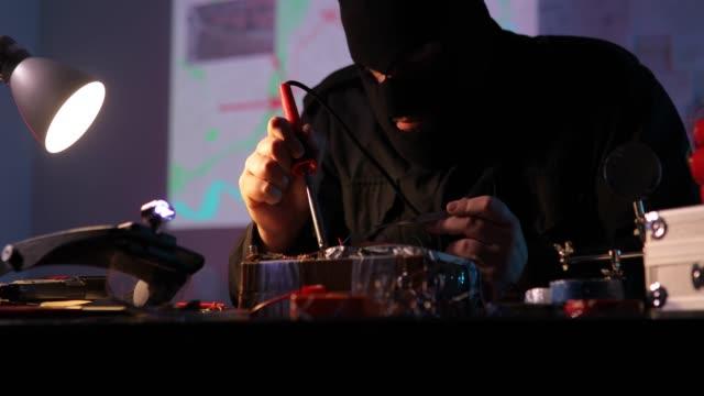 vídeos y material grabado en eventos de stock de terrorista construyendo una bomba en el taller - haz de luz